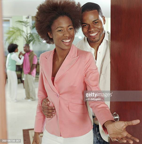 Young couple standing by open door, smiling