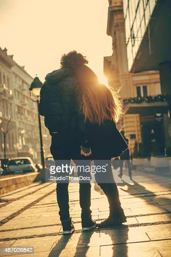 Young couple standing embraced on the street