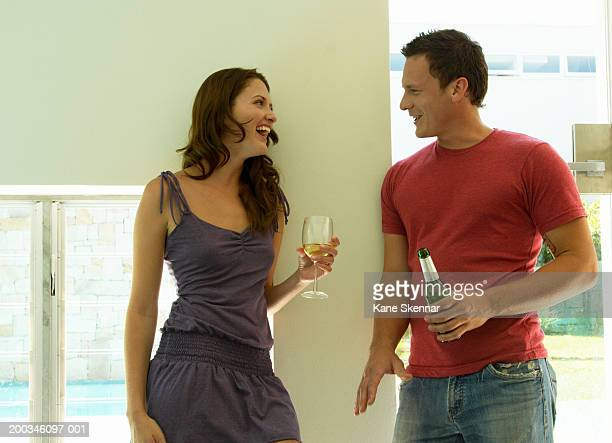 Young couple standing holding beer and wine, talking and laughing