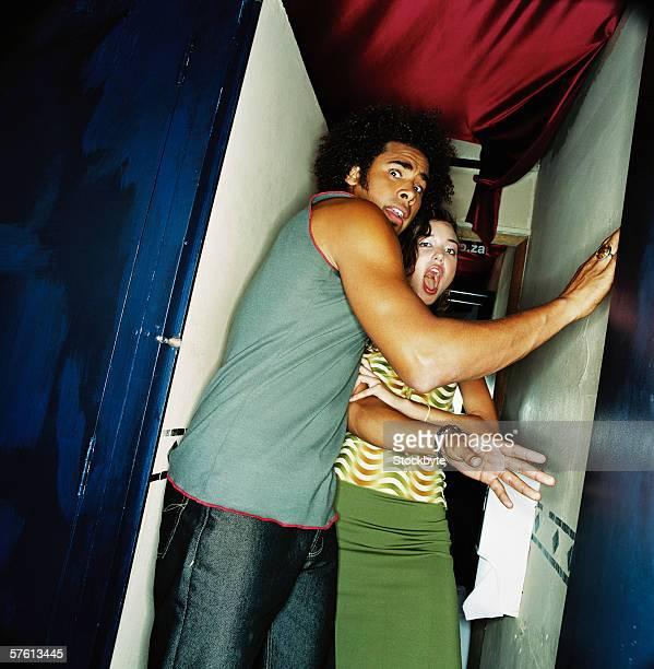 Young couple standing in a doorway in shock