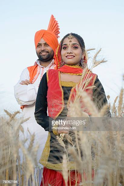 Young couple standing in a wheat field