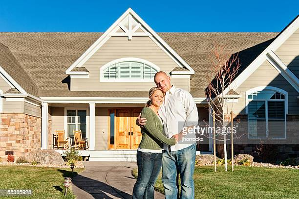 Young Couple Standing in front of New Home