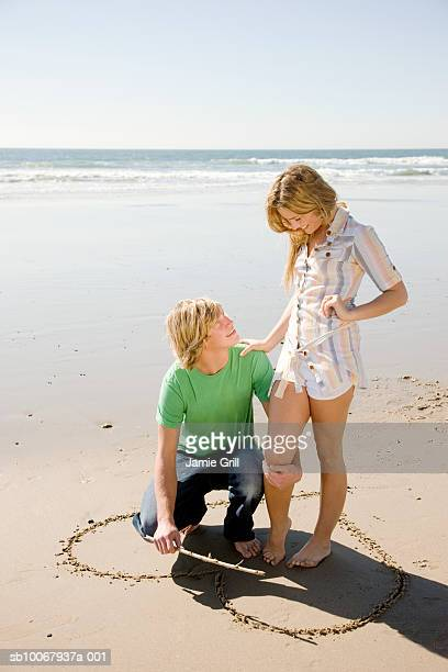 Young couple standing in heart drawn in sand