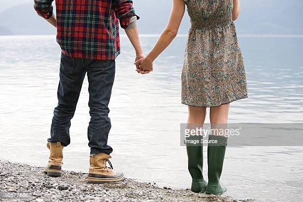 若いカップルは手を立つ湖