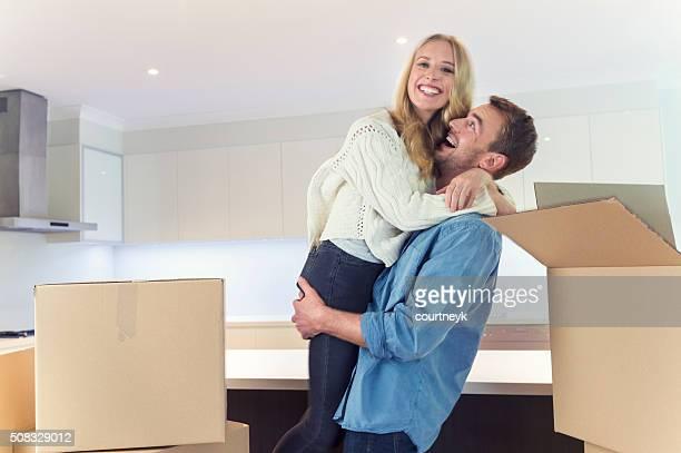 Jeune couple debout dans la nouvelle maison avec des boîtes de rangement.