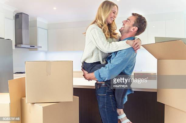 Young couple standing in new house with packing boxes.