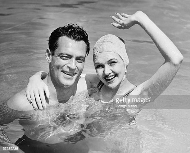 Young couple standing in pool, woman waving hand, (B&W), portrait
