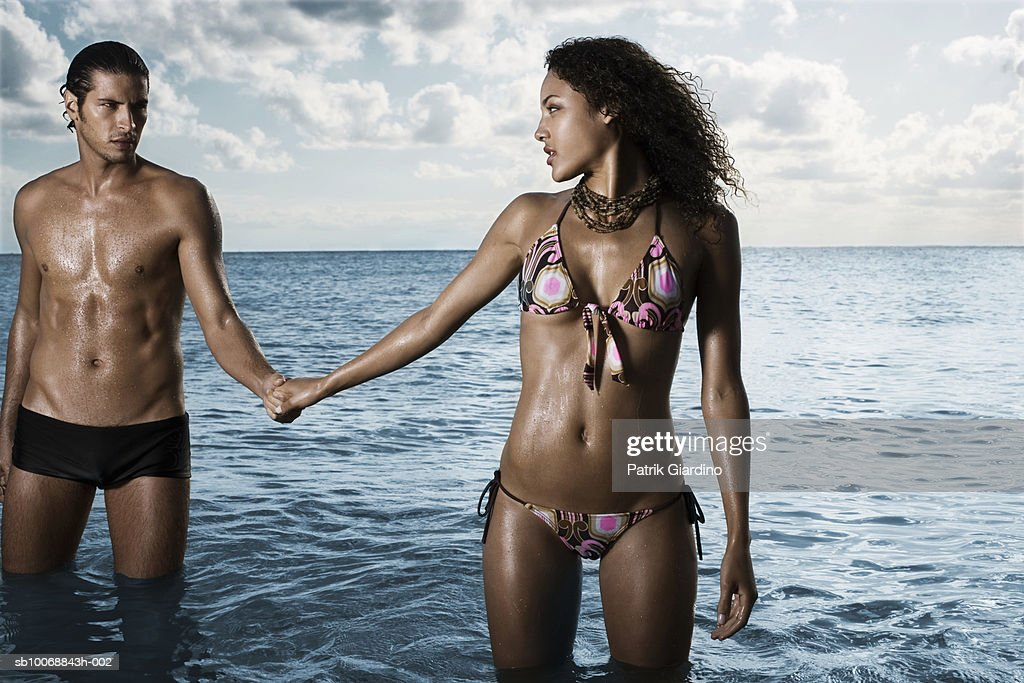Young couple standing in sea : Stock Photo