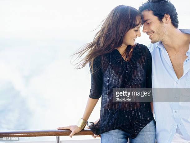 Young couple standing leaning against a railing of a boat