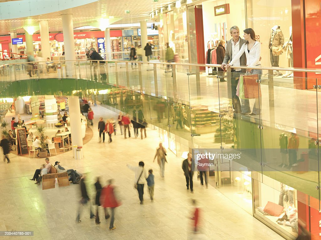 Young couple standing on balcony in shopping centre (blurred motion) : Stock Photo