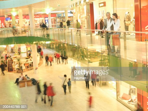 Young couple standing on balcony in shopping centre (blurred motion) : Bildbanksbilder
