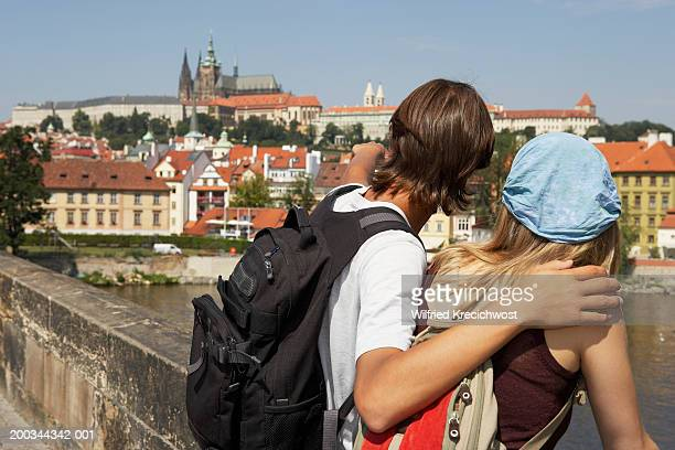 Young couple standing on Charles Bridge, pointing, rear view