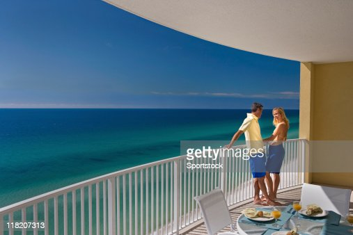 Young couple standing on hotel balcony overlooking ocean for Balcony overlooking city