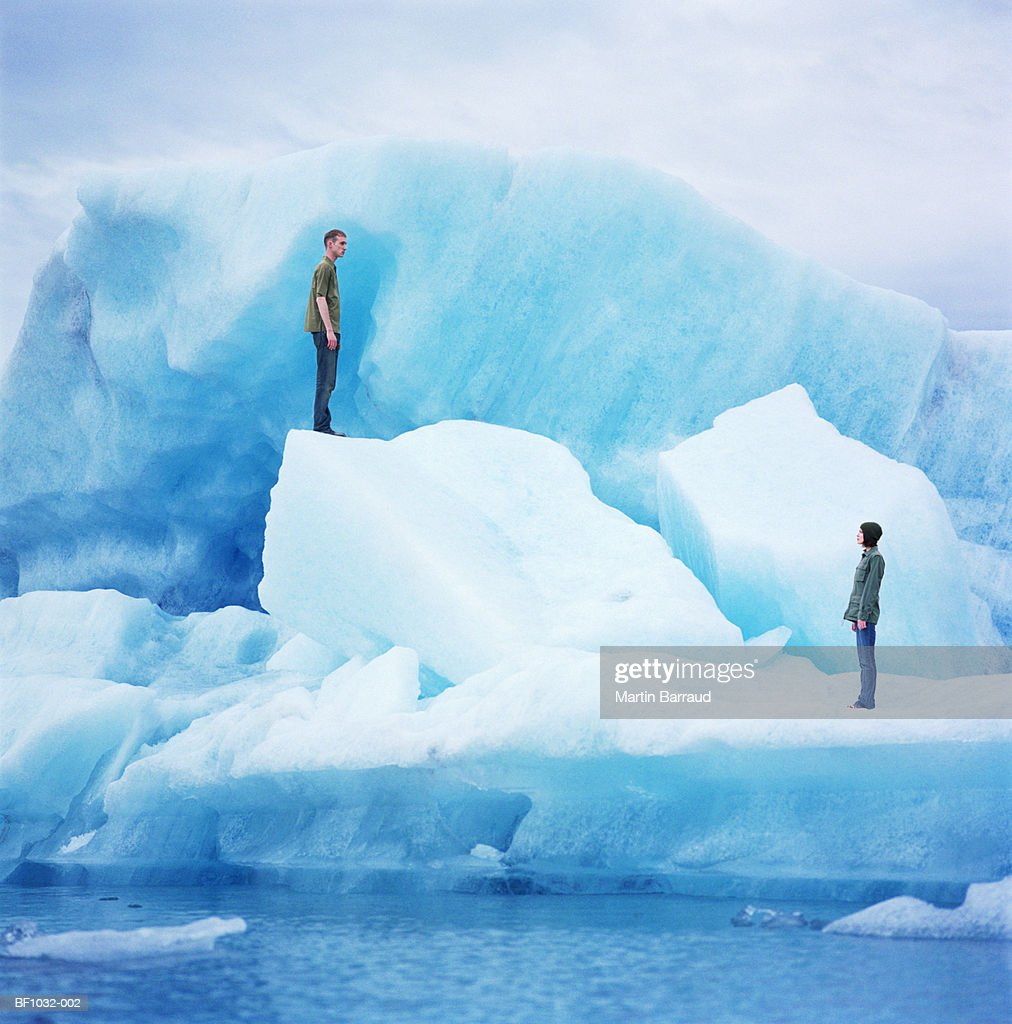 Young couple standing on icebergs, profile : Stock Photo