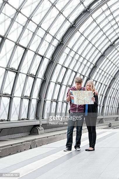 若いカップルの上に立つ鉄道駅のプラットフォームにマップお
