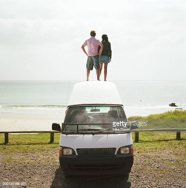 Young couple standing on roof of camper van on beach, rear view