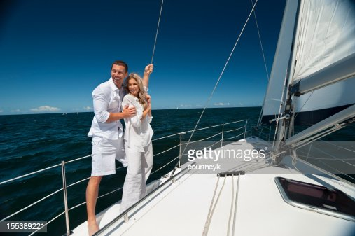 Young couple standing on sailboat cuddling each other
