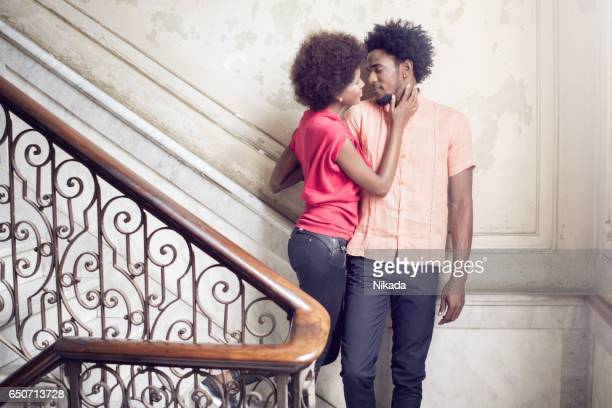 Young Couple standing on steps against wall, Havana, Cuba
