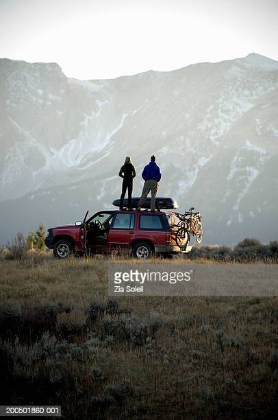 Young couple standing on SUV roof, looking at mountain view, rear view