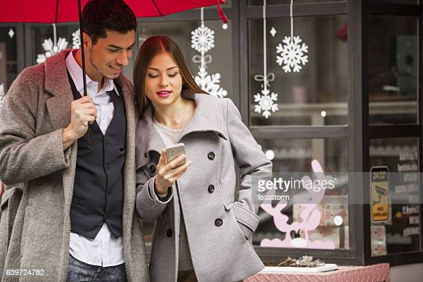 Young couple standing on the street checking their mobile device
