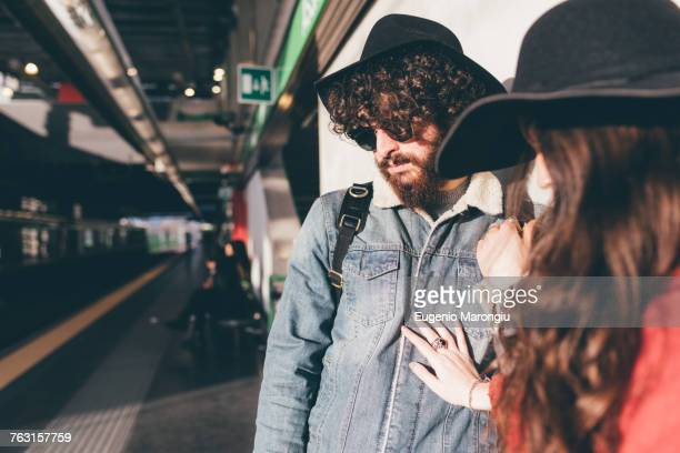 Young couple standing on train platform