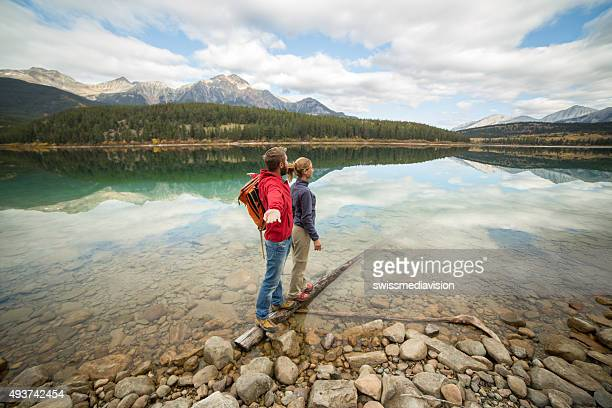 Young couple standing on tree log above lake enjoying nature