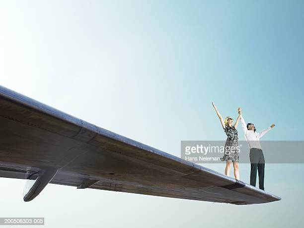 Young couple standing on wing of airplane, arms outstretched