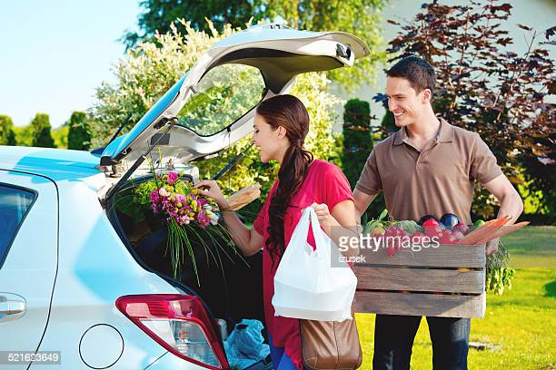 Young couple standing outdoor by car, came back from shopping