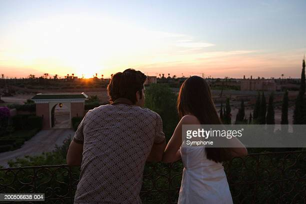 Young couple standing outdoors, sunset, rear view