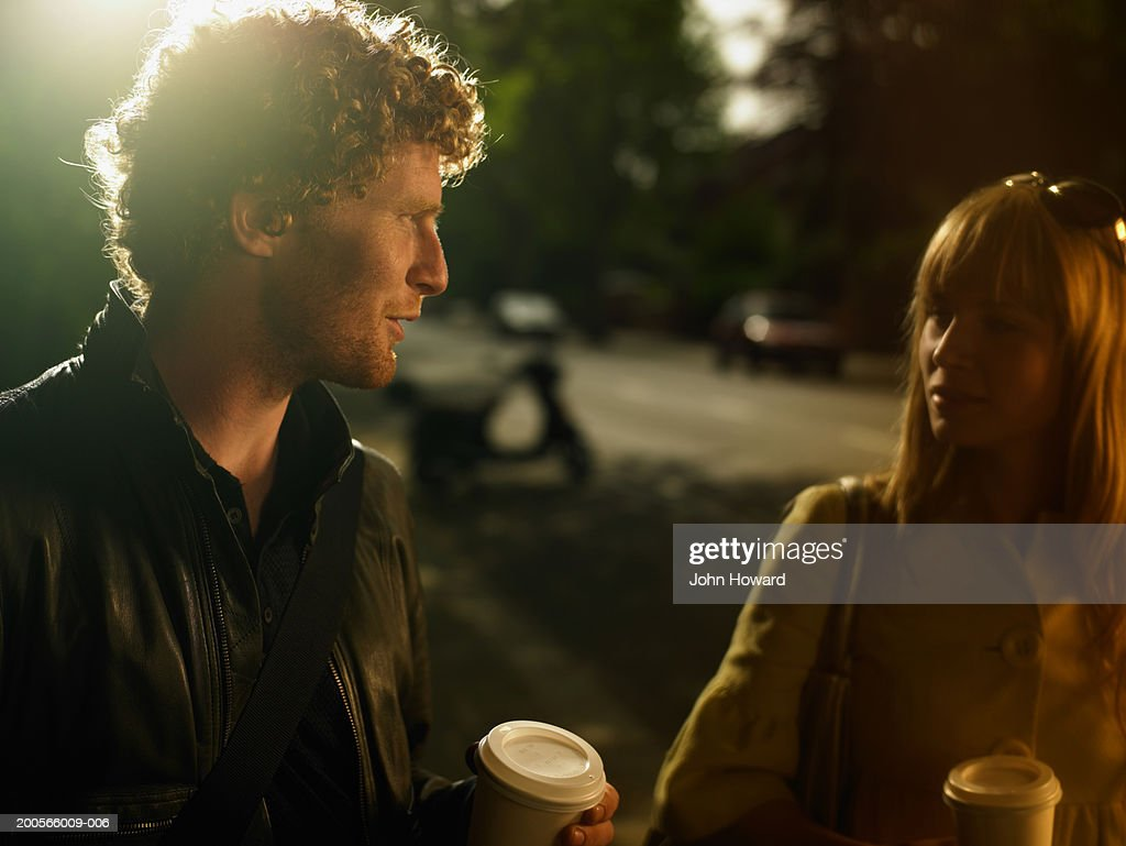 Young couple standing outdoors, with coffees : Stock Photo