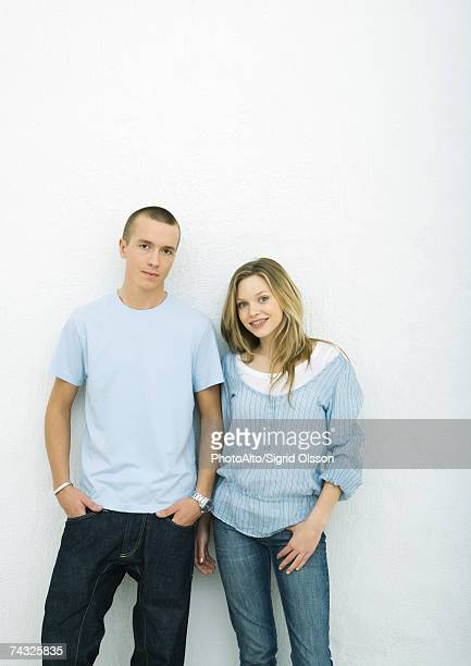 Young couple standing side by side, looking at camera, portrait, white background
