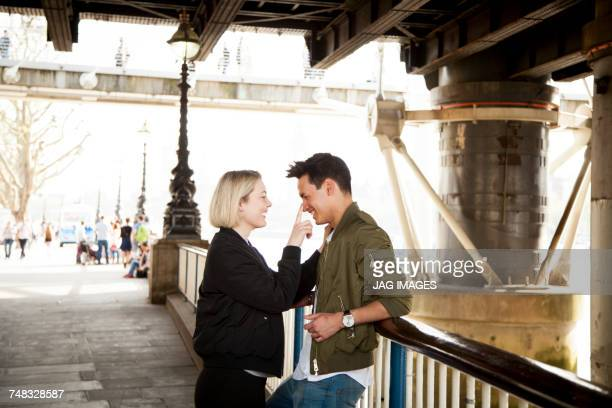 Young couple, standing underneath bridge, young woman touching mans face, smiling