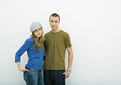 Young couple standing with hands in pockets, portrait, white background