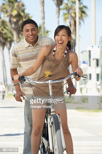 Young couple standing with tandem bicycle : Stock Photo