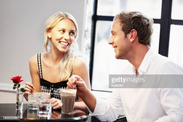 Young couple stirring coffee at cafe