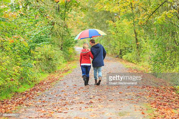 Young couple strolling along country lane with colorful umbrella