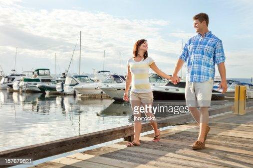 Young Couple Strolling Along Marina Boardwalk