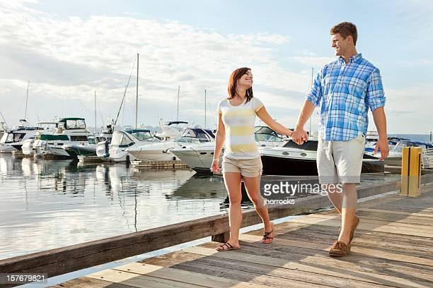 Young Couple Strolling Along Marina Boardwalk
