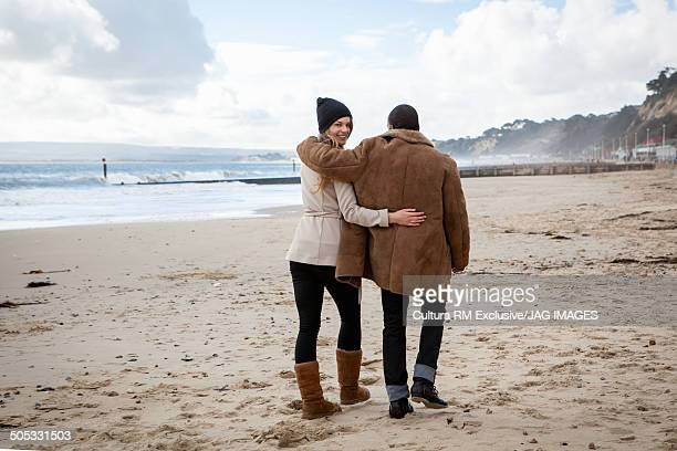 Young couple strolling on beach, Bournemouth, Dorset, UK