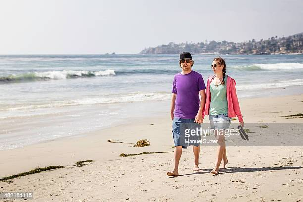 Young couple strolling on beach, Laguna Beach, California, USA