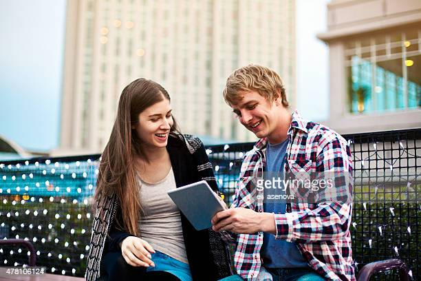 若いカップルでのネットサーフィンタブレット端末、東京外