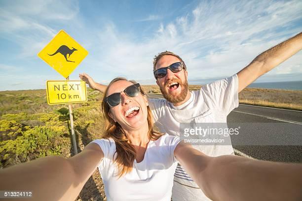 Jovem Casal tirar uma selfie Retrato perto de sinal de aviso de canguru na Austrália