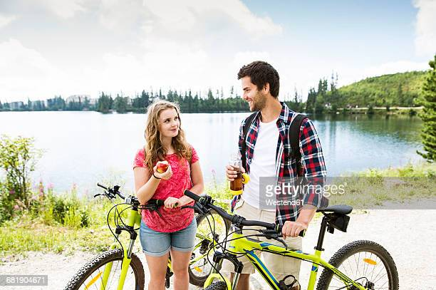 Young couple taking a break on a bicycle trip