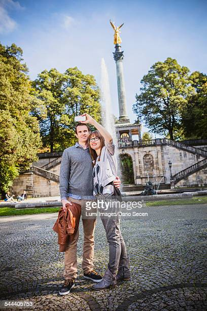 Young couple taking a self portrait against Angel of Peace Monument, Munich, Bavaria, Germany