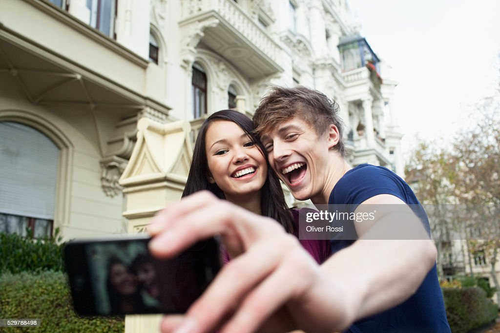 Young couple taking a self portrait : Stock Photo