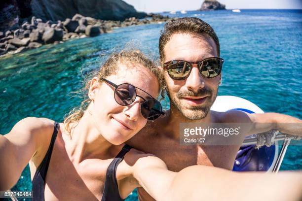 Young couple taking a selfie and relaxing over their luxury yacht deck