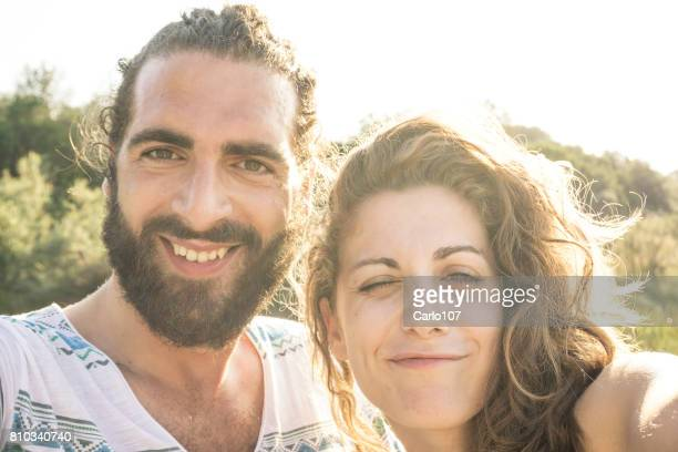 Young couple taking a selfie and winking