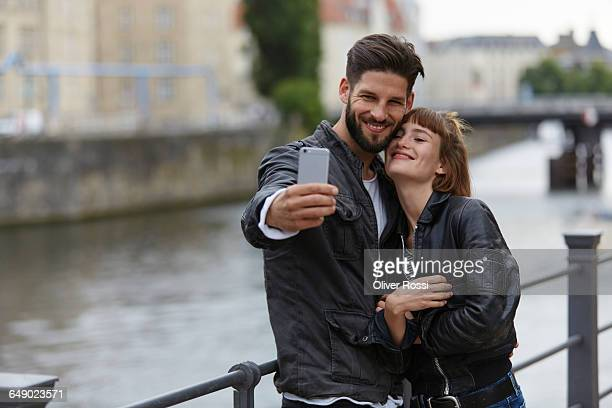 Young couple taking a selfie by the riverside