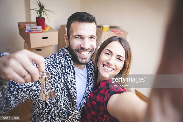 Young couple taking a selfie in their new home