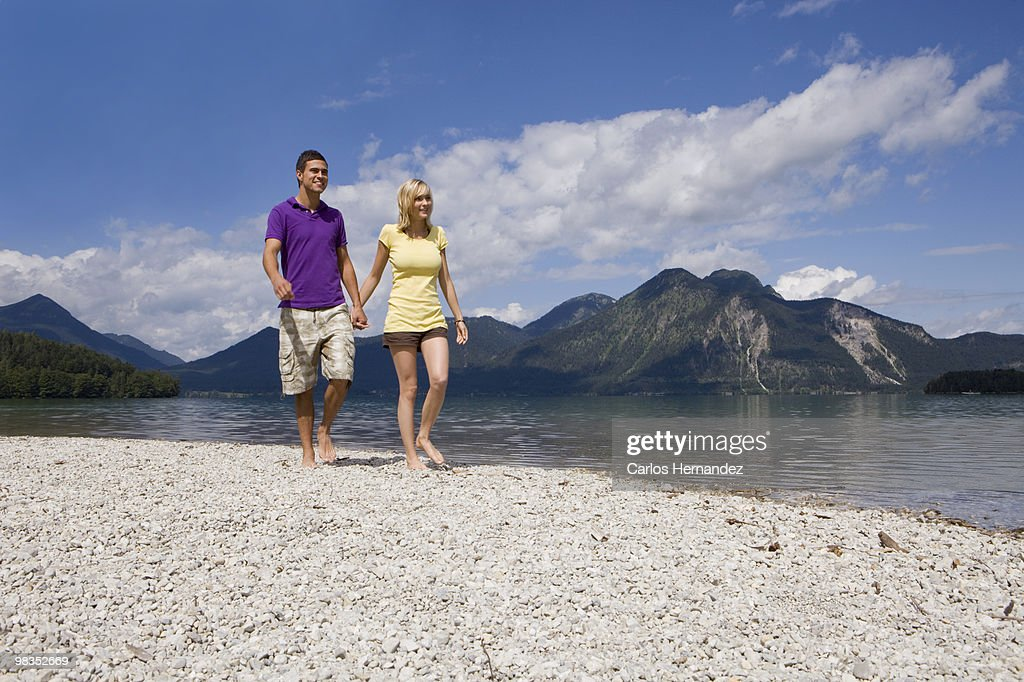 A young couple taking a walk by a lake : Stock Photo